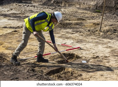 Driebergen, The Netherlands - March 22, 2017: Archeology excavation site with man digging in the ground in Driebergen, The Netherlands.