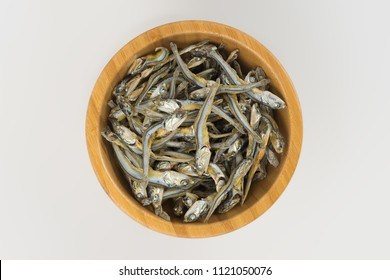 Dried anchovies used in Asian cuisine in wooden bowl white background isolated