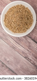 Dried anise seed or aniseed in white bowl over wooden background