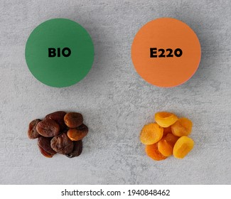 Dried apricot comparison. Apricot with preservatives (E220 Sulfur dioxide) and organic fruit without. Color difference. Dehydrated food pile.