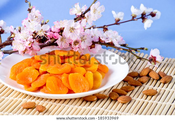 Dried apricots with almonds and blossoming branch on bamboo napkin