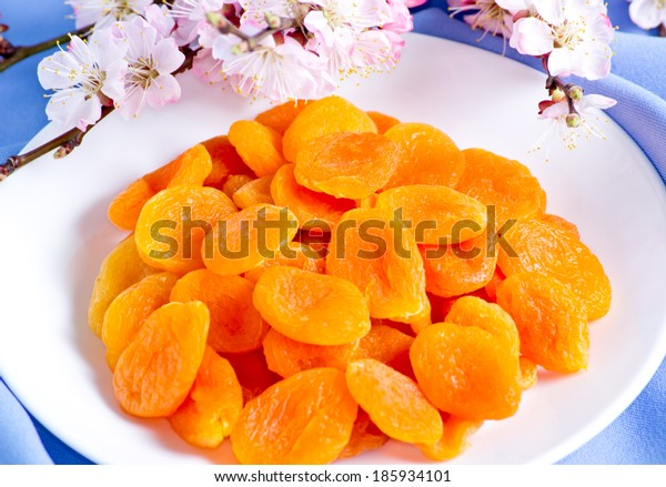 Dried apricots with almonds and blossoming branch on blue  fabric