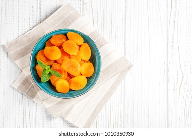 Dried apricots with mint in a bowl. Copy Space. The concept is healthy food, diet, vegetarianism.