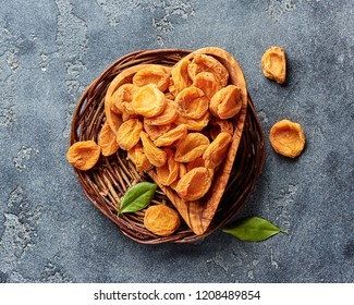 Dried apricots on gray concrete background. Top view.