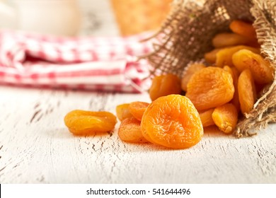 Dried apricots on white rustic wooden background