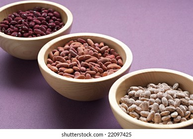 Dried assorted beans in wooden bowls