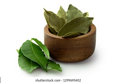 Dried bay leaves in a dark wood bowl next to fresh bay leaves isolated on white.