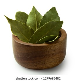Dried bay leaves in a dark wood bowl isolated on white.