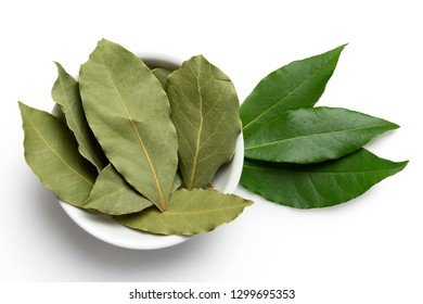 Dried bay leaves in white ceramic bowl next to fresh bay leaves isolated on white from above.