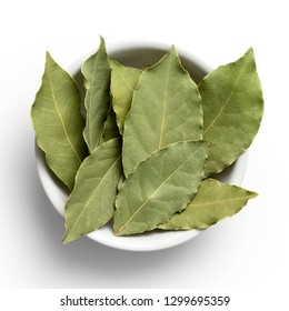 Dried bay leaves in white ceramic bowl isolated on white from above.