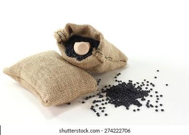 dried beluga lentils in sacks with bushels on a light background