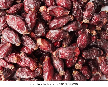 Dried berries of Dog Rose or Rosa canina. Dry fruits of sweet-brier or rose hips on wooden background. Healthy and herbal concept. Selective focus. Natural vitamin, nutritional supplement for health