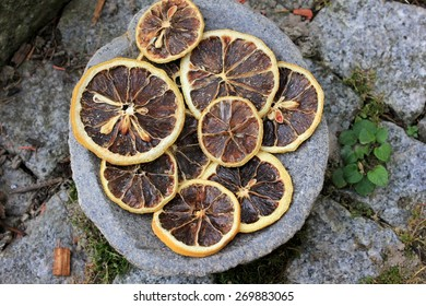 Dried blood orange slices, top view, on a grey stone pathway, with a natural scenic feeling, yellow and brown colored for christmas decoration and fragrance purposes