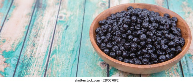 Dried blueberry in wooden bowl over wooden background