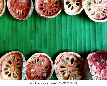 Dried brown and red slice bael in the green banana leaf background, texture, and natural framefor bael juice and drinking good for health in Asian food culture.