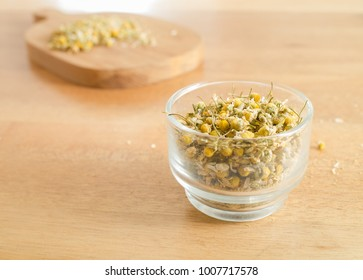 Dried Camomile in cup glass on wooden table