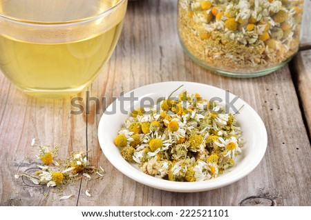 Dried camomile flowers on saucer. Chamomile tea in a transparent cup and dried camomile flowers on wooden table. Herbal tea for baby's stomach.