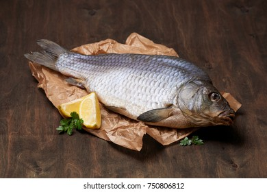Dried carp with lemon and greens on the crumped paper
