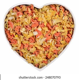 Dried carrots and onions in plate in the form of heart on a white background