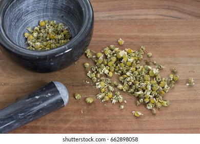 dried chamomile flower heads in mortar