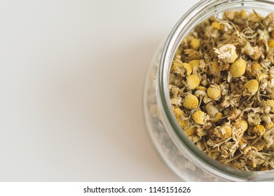 Dried chamomile flowers in a jar on white table. Herbal tea