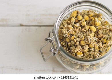 Dried chamomile flowers in a jar on wooden table. Herbal tea. Healthy drink