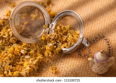 dried chamomile flowers and metal strainer