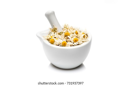 Dried chamomile flowers in mortar on white background