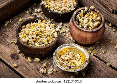 Dried chamomile flowers on wooden table.Alternative medicine.Bowls of dry medicinal herbs