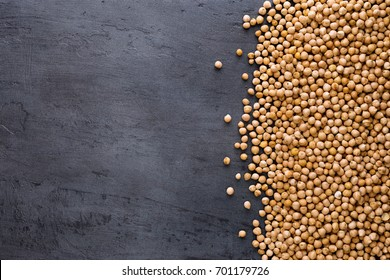 Dried chickpeas on dark surface with border, top view