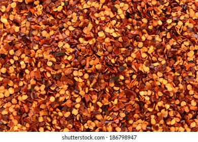 Dried chili flakes and seeds, or crushed red pepper, abstract background texture