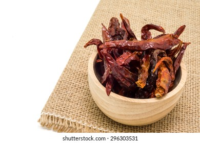 Dried chili in wooden bowl isolated on white background.