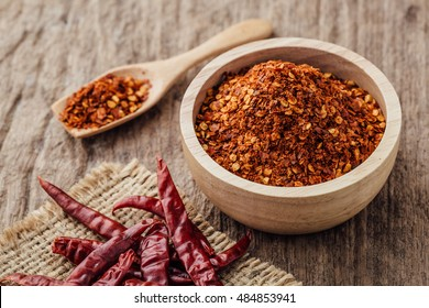 dried chilli and powder chilli on wooden table