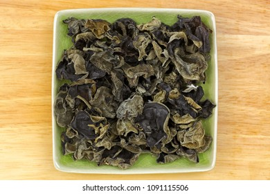 Dried Chinese edible black fungus, called Jew's Ear Mushroom in green dish, top view on wooden background