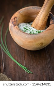 Dried Chives Herb in Wooden Mortar and Pestle to make Herb Salt; Fresh Sprig of Herb on Wooden Tabletop