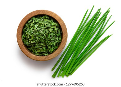 Dried chopped chives in a dark wood bowl next to a pile of whole fresh chives isolated on white from above.