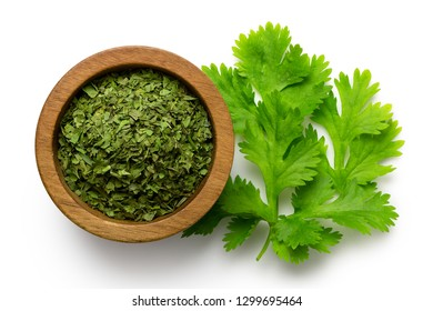 Dried chopped coriander leaves in a dark wood bowl next to fresh coriander leaves isolated on white from above.