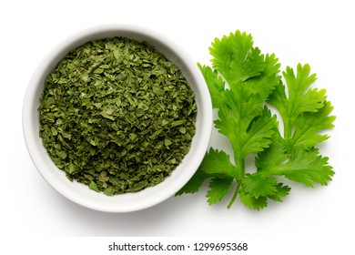 Dried chopped coriander leaves in white ceramic bowl next to fresh coriander leaves isolated on white from above.