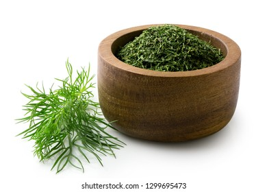 Dried chopped dill in a dark wood bowl next to fresh dill leaves isolated on white.