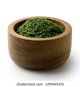 Dried chopped dill in a dark wood bowl isolated on white.