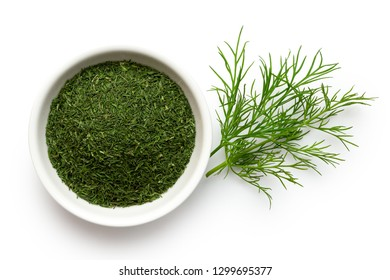 Dried chopped dill in white ceramic bowl next to fresh dill leaves isolated on white from above.