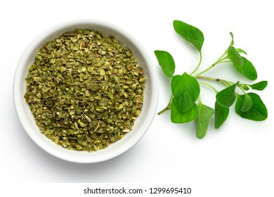 Dried chopped oregano in white ceramic bowl next to fresh oregano leaves isolated on white from above.