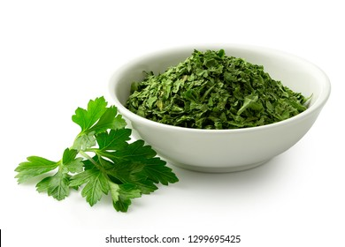 Dried chopped parsley in white ceramic bowl next to fresh parsley leaves isolated on white.