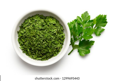 Dried chopped parsley in white ceramic bowl next to fresh parsley leaves isolated on white from above.