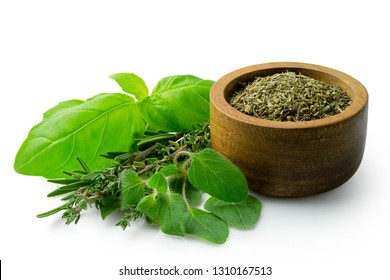 Dried chopped provence herbs in a dark wood bowl next to fresh bouquet garni isolated on white.