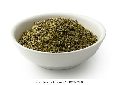 Dried chopped provence herbs in a white ceramic bowl isolated on white.