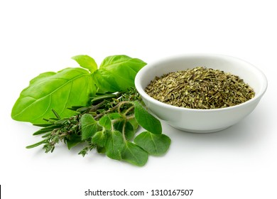 Dried chopped provence herbs in a white ceramic bowl next to fresh bouquet garni isolated on white.