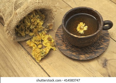 Dried Chrysanthemum flower in burlap sack and cup of Chrysanthemum tea over wooden background. The tea is considered a herbal drink.