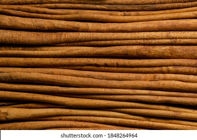 Dried cinnamon bark strips background. A brown spice from the inner bark of Cinnamomum verum, the true cinnamon tree. Aromatic condiment and flavouring additive. Close-up from above, macro food photo.