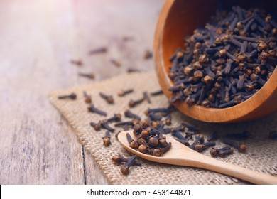 dried cloves on wooden spoon and  background.